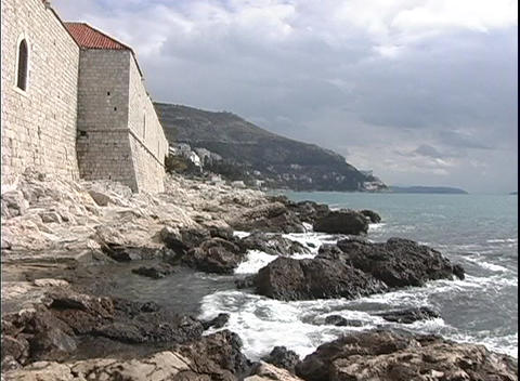 Houses along the Dubrovnik coast meet with the rocky shoreline Footage