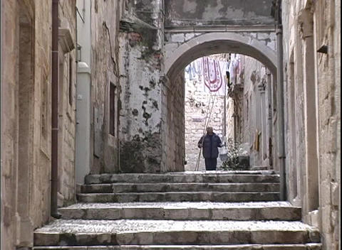 The camera zooms-in to man walking down an alley returning to his home in Dubrovnik, Croatia Footage