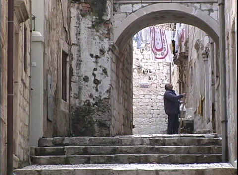 The camera zooms-in to man walking down an alley... Stock Video Footage
