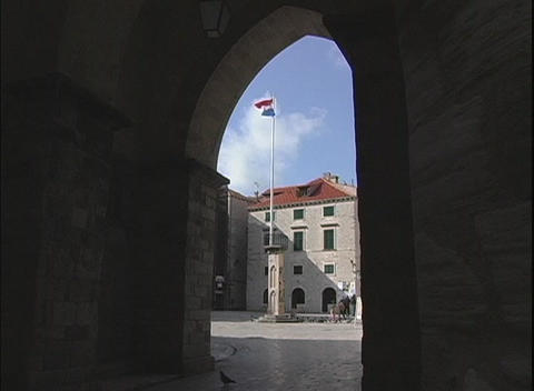 Viewed through an archway, the Croatian flag moves gently in the wind Footage