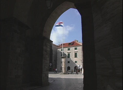 Viewed through an archway, the Croatian flag moves gently... Stock Video Footage