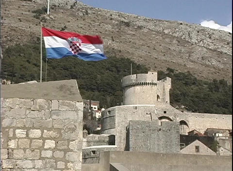 A Croatian flag blows in the wind over a castle in Dubrovnik Footage