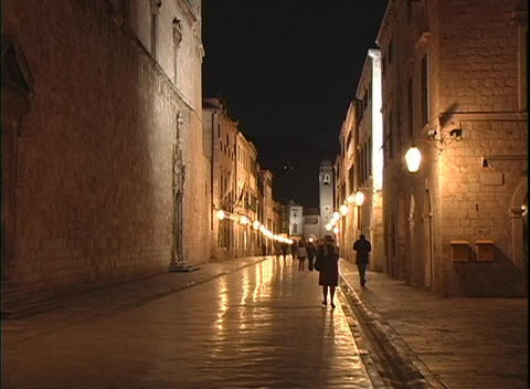 People walk along narrow streets in Dubrovnik, Croatia at night Footage