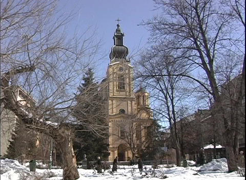 People, walking in the snow, pass by a church in Bosnia Stock Video Footage