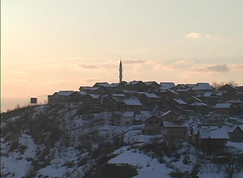 Snow covered houses on a hilltop display a Bosnian winter during golden-hour Footage