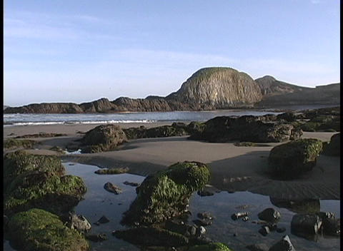 The ocean lapping the beach at low tide along a rocky... Stock Video Footage