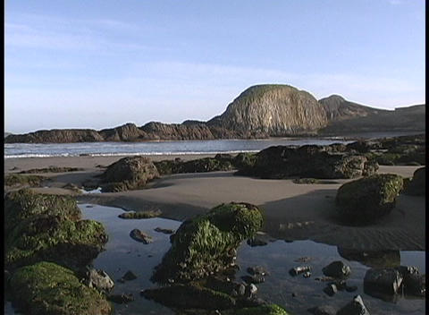 The ocean lapping the beach at low tide along a rocky shore of the Oregon Coast Footage