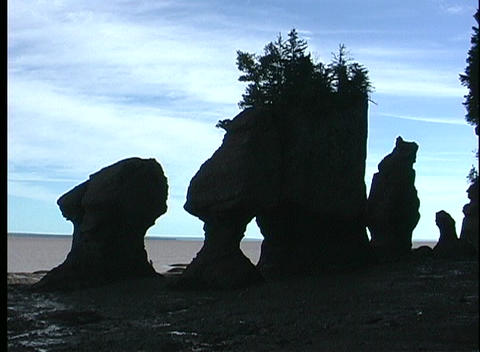 A medium-shot of head shaped silhouetted rocks along the shoreline of the Bay of Fundy Footage
