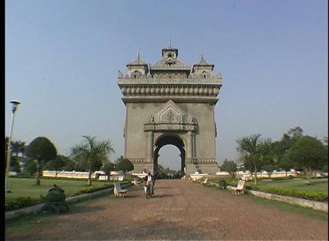 A man rides his motorcycle toward the camera after passing through a large arched monument Footage