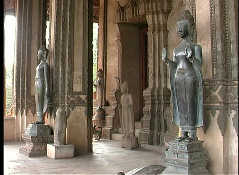 Buddhist statues stand at the entrance to a temple in Laos Footage