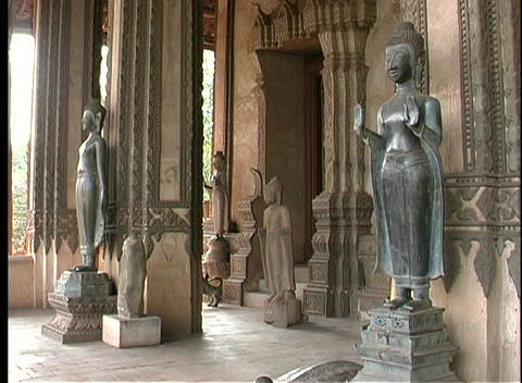 Buddhist statues stand at the entrance to a temple in Laos Stock Video Footage