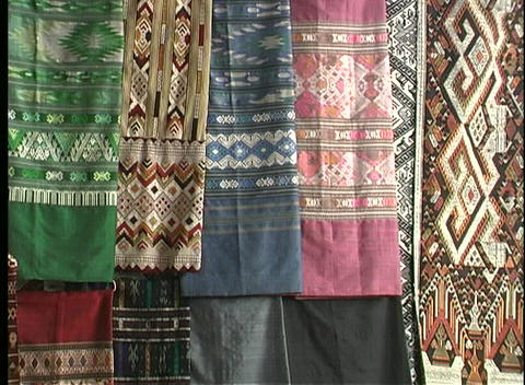 Colorful fabric hangs in an open market on shopping day in Vientiane, Laos Footage