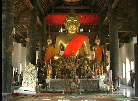 A huge golden Buddha statue and many smaller statues are... Stock Video Footage