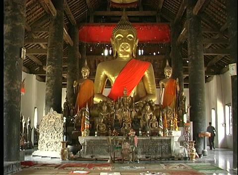 A huge golden Buddha statue and many smaller statues are the focal point in a stupa in Vientiane, La Footage