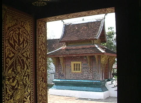 A small Buddhist temple seen through a doorway in Asia Stock Video Footage
