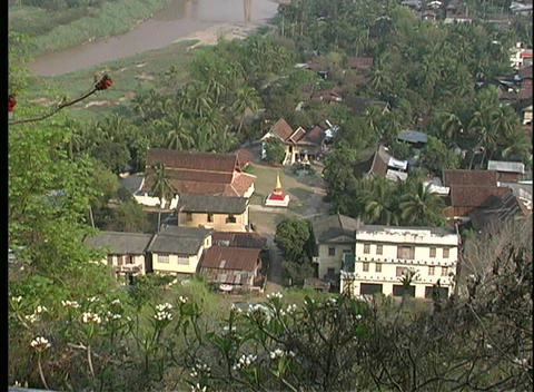 A aerial view of a small religious community near a river and forest in Laos Footage