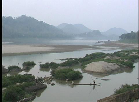 A beautiful view of a river in Asia with fishermen in longboats, and majestic mountains in the backg Footage
