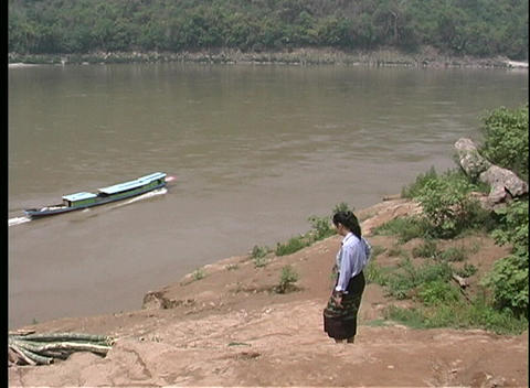 A woman walks along a shoreline and watches a long barge travel along a muddy river in Laos Footage