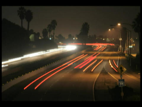 Time-lapse of traffic driving in both directions on a city highway at night Footage