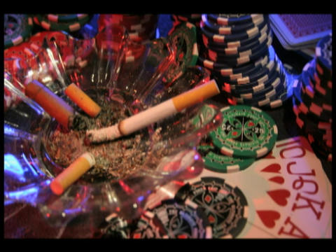 Time-lapse Of A Cigarette Burning In An Ashtray Surrounded By Poker Chips And Playing Cards stock footage