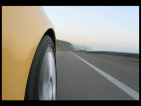 Time-lapse of a yellow car driving on a coastal highway Stock Video Footage