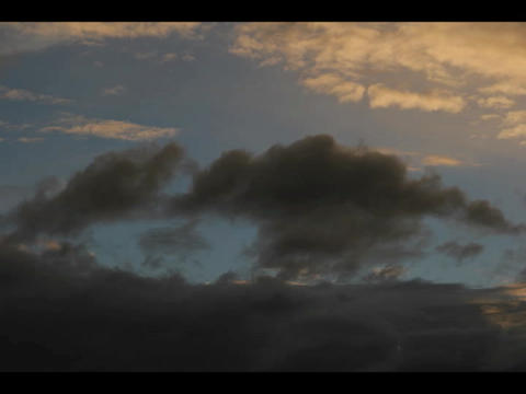 Time-lapse of storm clouds moving across a darkening blue... Stock Video Footage