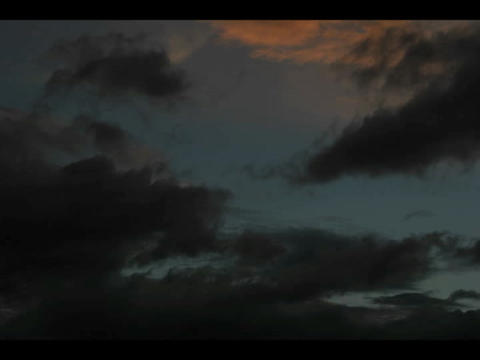 Time-lapse of storm clouds moving across a darkening blue sky Footage