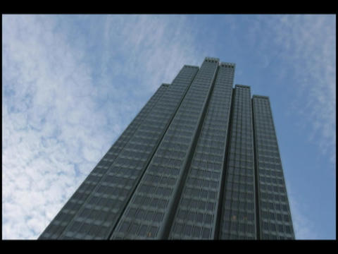 Time-lapse of clouds moving through a blue sky above a skyscraper Footage