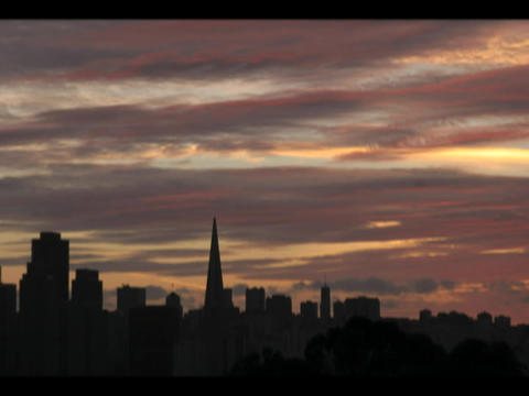 The San Francisco skyline is silhouetted by a darkening sky Stock Video Footage