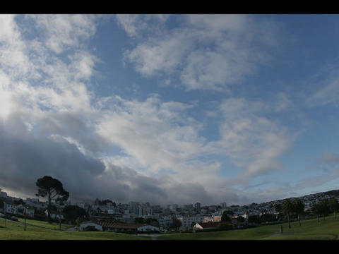Time-lapse of blue sky and clouds over a small city Stock Video Footage