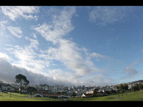 Time-lapse of blue sky and clouds over a small city Footage