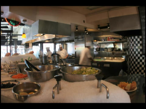 Time-lapse of chefs and cooks preparing food in a professional kitchen Footage