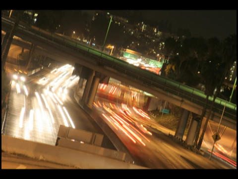 Time-lapse of city traffic on a highway and overpass at night Footage