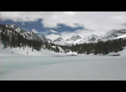 Rugged mountains rise behind a frozen lake in a wilderness area Footage