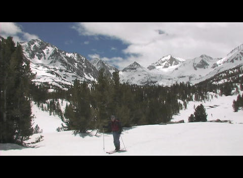 A skier stands holding his pole on a snow-covered mountain Footage