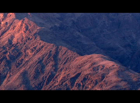 One side of a mountain range glows colorfully while the other is dark Footage