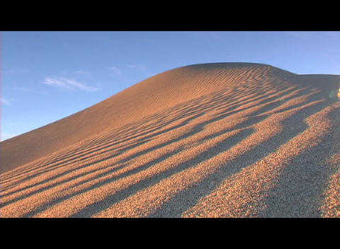 Golden light shines on sand dune furrows Stock Video Footage