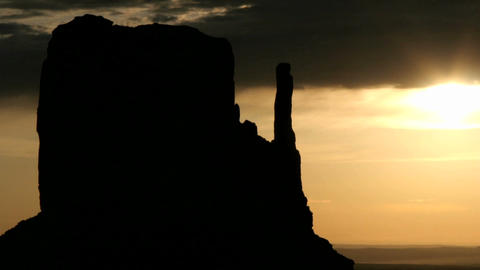 A colorful sky silhouettes Mitten Buttes in Monument Valley, Utah Footage