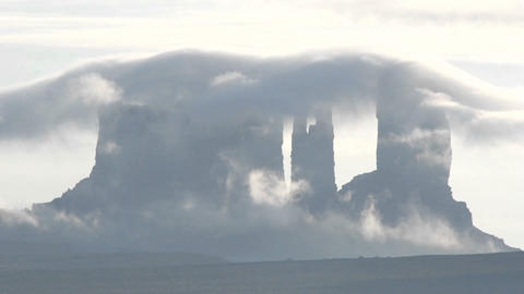 Wispy dark clouds move quickly over rock formations in... Stock Video Footage