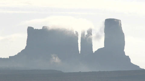 Wispy dark clouds move quickly over rock formations in Monument Valley, Utah Footage