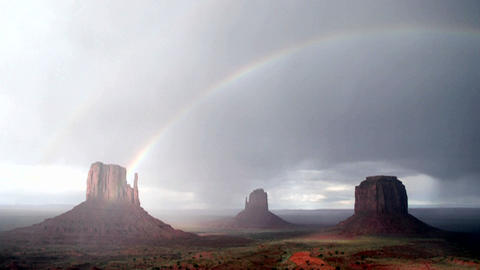 A rainbow forms in the sunlight following a storm over Monument Valley, Utah Footage