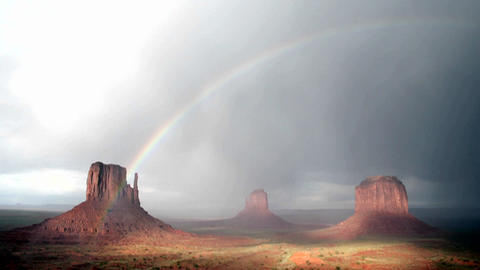 A rainbow forms in the sunlight following a storm over... Stock Video Footage