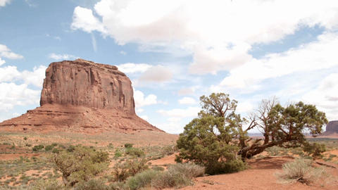 White clouds move quickly over a butte in Monument Valley's Navajo Tribal Park Footage