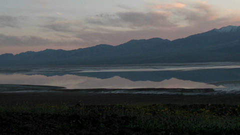 A colorful sky becomes dark over a pristine lake in Death Valley National Park Footage