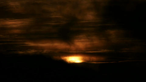 Clouds move quickly over the orange sun in a darkening sky Stock Video Footage