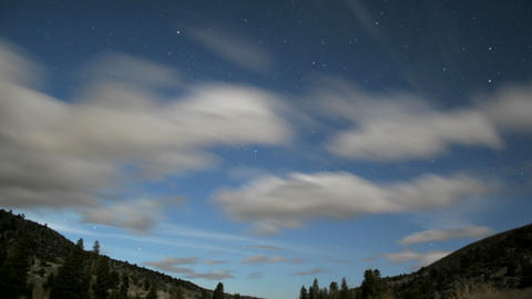 Fluffy white clouds race through a blue sky as it fades... Stock Video Footage