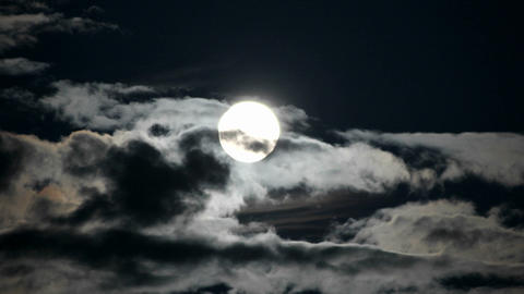 A bright full moon rises as clouds move quickly in a night sky Footage