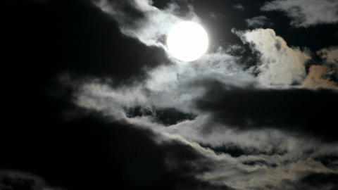 A bright full moon rises as clouds move quickly in a... Stock Video Footage
