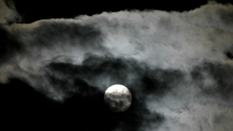 A bright full moon rises above swiftly moving clouds in the night sky Footage