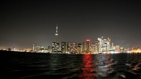 The bright Toronto skyline approaches in a time-lapse from the water Footage